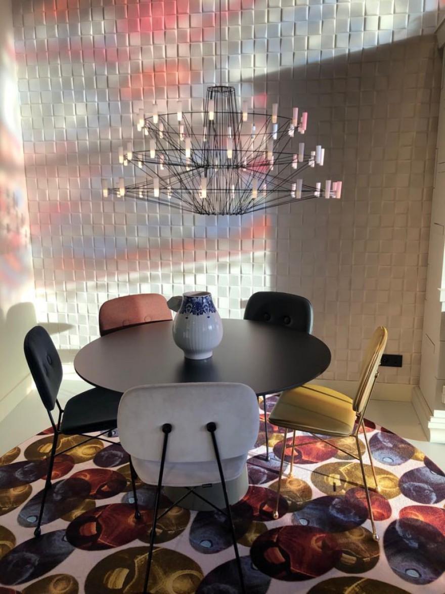 Lustre Coppelia noir au-dessus de la table ronde avec les chaises dorées